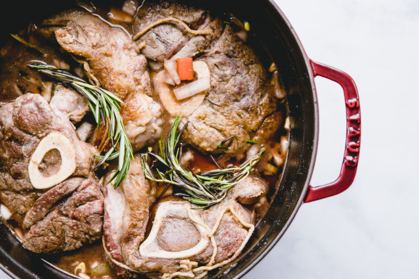 Beef Shank Osso Bucco in a red staub dutch oven with rosemary sprigs