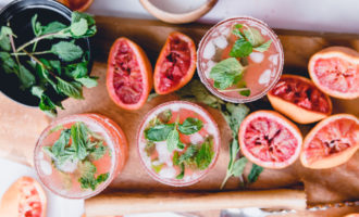 Blood Orange Kombucha Mojito on wooden tray with wooden muddler and mint leaves in a bowl of water