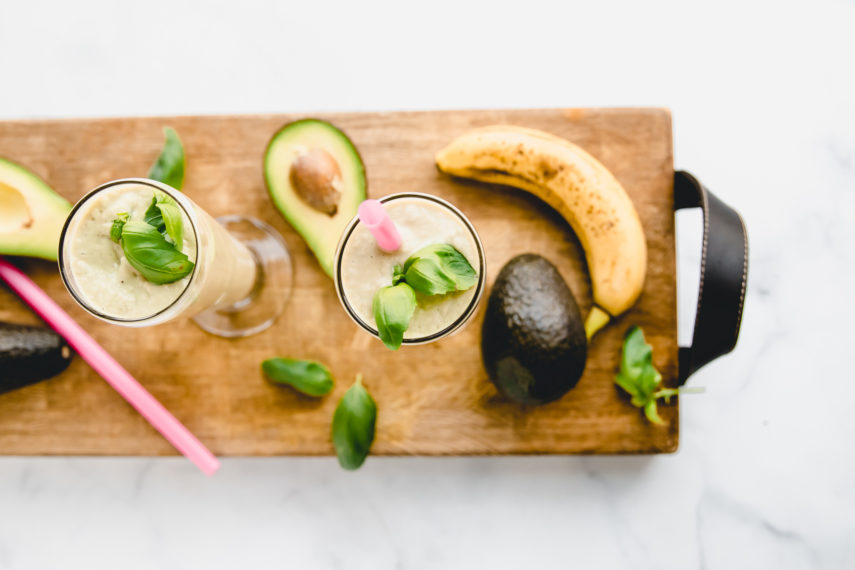 Avocado Basil Morning Smoothie. Made with avocado, basil, banana,pineapple, and coconut milk. Smoothies are on a William Sonoma charcuterie cutting board