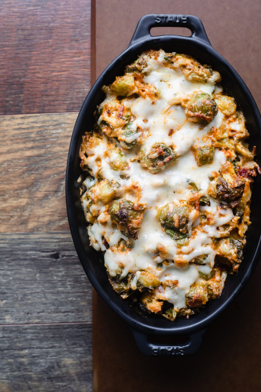 baked hot cheesy brussel sprout and bacon dip in black staub