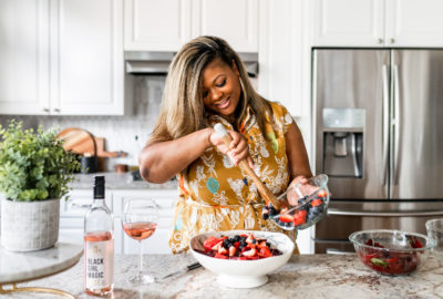 watermelon salad with berries and roasted beets, black woman making a salad in an Anthropologie dress
